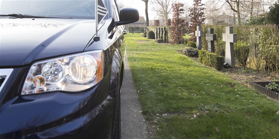 Begrafenisauto rijdt over een kerkhof