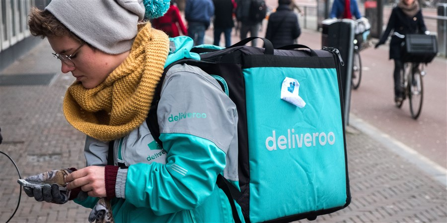 Deliveroo maaltijdbezorger checkt haar smartphone