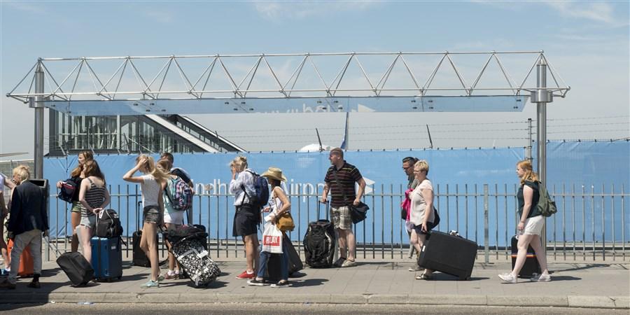 Mensen met koffers op wieltjes lopen op vliegveld Eindhoven