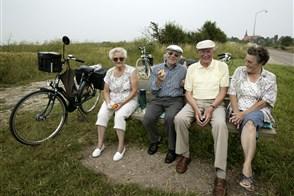 Ouderen rusten uit van fietstochtje op een bankje